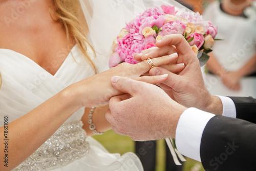 Leinwanddruck Bild groom putting ring on bride's finger