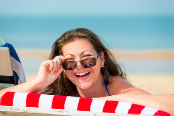 portrait of a laughing girl on the beach in a deckchair