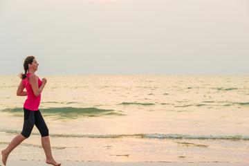 woman running barefoot on the sandy beach