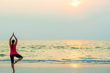 slender girl balancing on one leg. Yoga on the beach