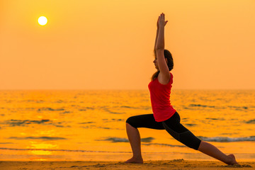 woman engaged in yoga at sunset near the ocean