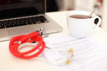 Arbeitsplatz mit Unterlagen und Stetoskop