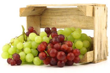 red and white grapes in a wooden box on a white background