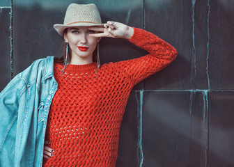 Young beautiful hipster girl in red jersey with hat near wall