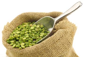 split green peas in a burlap bag on a white background