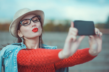 Beautiful young girl in the hat taking picture of herself, selfi