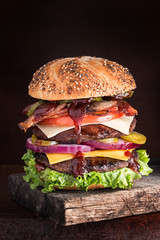Double decker cheeseburger with many ingredients on seeded bun