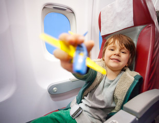 Smiling boy with toy plane flying on jet airplane