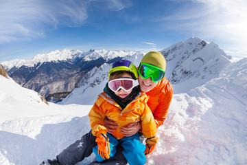 Little skier, father sit in snow on mountain peak
