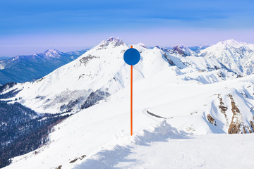 Blue attention sign on winter Caucasus mountains