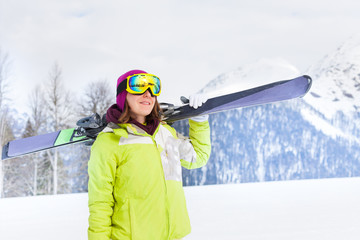 Beautiful woman in mask standing and holding ski