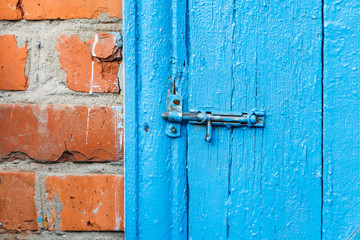 closed catch on old blue painted door of shed
