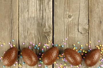 Chocolate Easter egg bottom border on wood