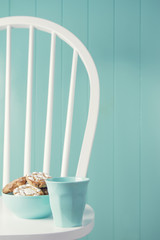 A bowl with cookies and a glass on a white windsor chair