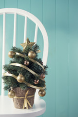 A christmas tree on a windsor chair beside a turquoise wainscot.