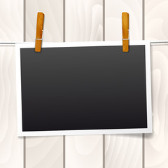 Frame hanging on a rope on wooden background