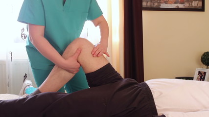 Physical therapist giving a knee massage to young man.