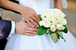 hands of the bride and groom with rings on a background of a wed