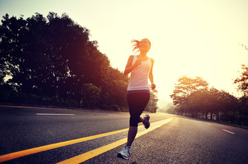 young woman runner running at sunrise road