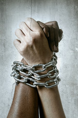 white race hand chain locked together with black ethnicity hand