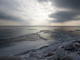 Afternoon winter sky casts a glow on frozen water of Lake Erie