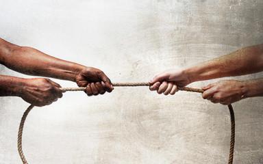 black ethnicity hands pulling rope against white Caucasian race