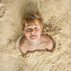 happy young boy covered by fine sand