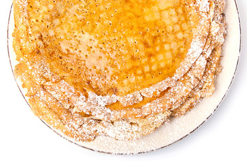Slim pancakes with honey and powdered sugar on white background