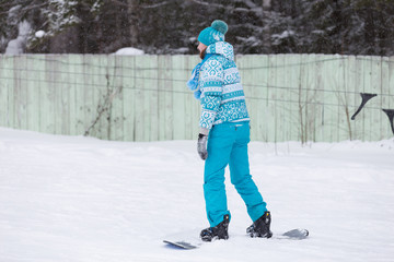 Girl on a snowboard in a blue suit