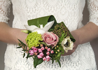 Bridal bouquet, small and delicate, against white lace dress