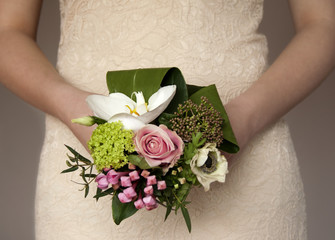 Bridal bouquet, small and delicate, against natural lace dress