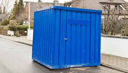 Ein blauer Werkzeugcontainer steht am Strassenrand