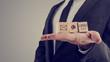 Leinwanddruck Bild - Businessman holding three wooden cubes with contact symbols