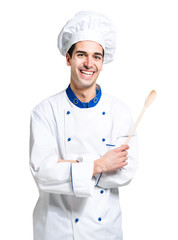 Young smiling chef isolated on white holding a spoon