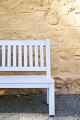 Gartenbank in einem Park an einer Kirchenmauer