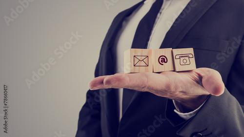 Leinwanddruck Bild Businessman holding three wooden cubes with contact symbols