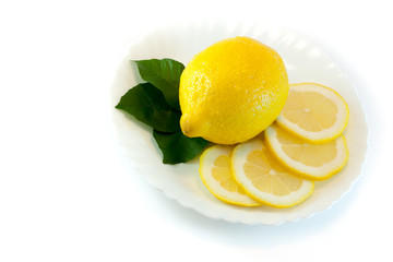 Lemon with leaves and slices on the plate