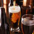 pouring beer into glass on wooden table - 78661256