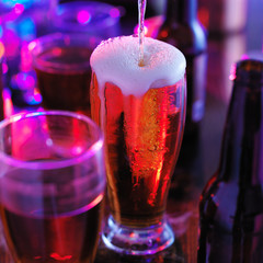 pouring beer into overflowing glass with colorful lights at bar