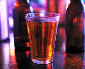 cup of beer in colorful lighting at bar shot eye level