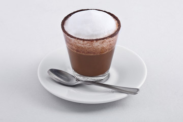 close up of small coffee cup with cream on white background