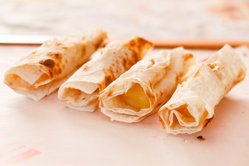 Grilled rolls of bread lavash with cheese suluguni