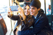 Young couple taking selfies with smartphone at bus. - 78663206