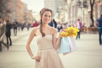 Portrait of smiling young woman shopping in a town
