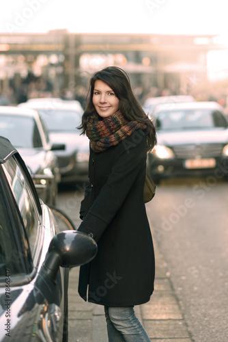 canvas print picture Modische Frau öffnet ihr Auto an der Straße