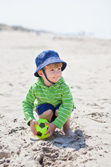 Two years old boy playing on sand beach.