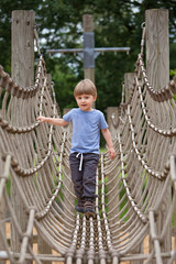Little boy climbing a rope bridge at playground.