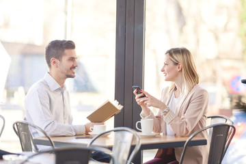Two young business people sitting in a cafe