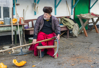 Ukrainian peasant getting ready to whet a scythe
