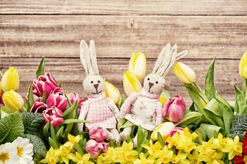 Osterhasen auf Holz und Blumen
